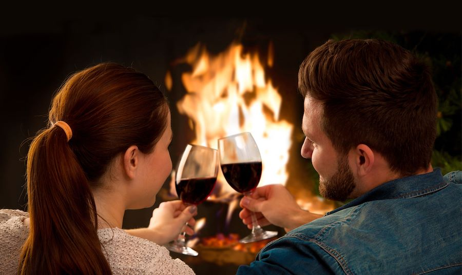 Couple with wine in front of fire in fireplace